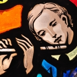 Stained Glass portait of Stephen Foster, playing a flute, close-up